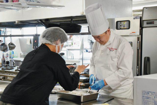 子供向け料理動画で紹介するグラタンを作る金子総調理長(右)